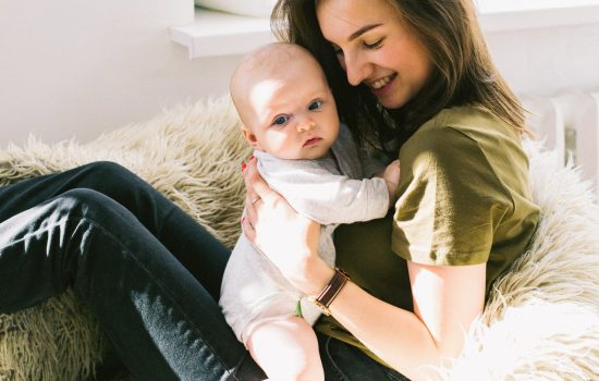 woman-in-green-shirt-holding-baby-while-sitting-698877